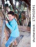 Cute little boy exploring rustic beach hut - stock photo