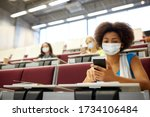 education, healthcare and pandemic concept - african student girl wearing face protective medical mask for protection from virus disease with smartphone at lecture
