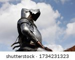 Mounted knight in full plate armour. Man reenacting late Middle Ages knight in full plate armour and chainmail with hounskull shaped bascinet, mounted on a horse. Blue sky with clouds in background.