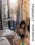 Small photo of Selective focus of woman in medical mask cleaning table while child holding dust brash at home