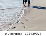 Father and daughter footprints at beach - stock photo