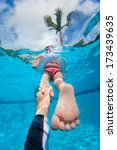 Father holding his little daughter feet while she swims - stock photo