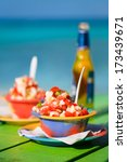 Two bowls of Bahamian conch salad and bottle of beer - stock photo