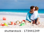 Father and daughter on beach during summer vacation - stock photo