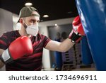 Small photo of Young caucasian male wearing red boxing gloves & protective face mask,hitting blue sack in a reopen indoor gym,Coronavirus COVID-19 pandemic imposing social distancing rules and cautionary measures