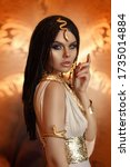 Small photo of woman queen Cleopatra art photo. Creative golden makeup Black hair braids. Carnival ethnic egypt costume dress. Accessories jewelry snake bracelet, crown. Fashion model girl beautiful face close-up