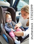 mother putting baby into car... | Shutterstock . vector #173523599