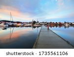Sailing and fishing boats moored to a pier in yacht marina at sunset. Colorful cloudscape, reflections on the water. Sailing, recreation theme. Village in South Norway - stock photo
