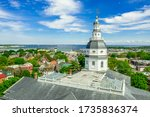 Small photo of Aerial view of Maryland State House capitol building white dome with two-stage drum and lantern and splayed pent roof Annapolis town in the background on a sunny weekend afternoon