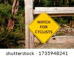 """""""Watch for cyclist"""" sign. Yellow metal sign mounted on nature wood fence. Warning message on multi purpose trail /path for hikers and downhill mountain bikers. Blurred forest background. - stock photo"""
