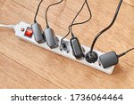 Small photo of Electrical power strip overloaded with multiple electrical cords plugged in. Many plugs plugged into electric power bar