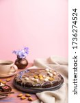 Homemade chocolate brownie cake with caramel cream and almonds with cup of coffee on a colored and pink background and linen textile. Side view, copy space, selective focus. - stock photo