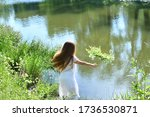 Beautiful girl in white dress putting flowers wreath on river water surface.Feast of Ivan Kupala.Midsummer. Earth Day.Pagan holiday of Ivan Kupala.Selective focus