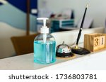 Small photo of Coronavirus ( Covid-19 virus ) hand sanitizer gel or alcohol ge to wash hands at modern luxury hotel reception counter desk with bell,Pen and woodcalendar . product for airport, hospital