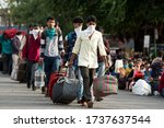 Small photo of MUMBAI/INDIA - MAY 21, 2020: Migrant workers sits in queues at railway terminus for boarding a special train back home during a nationwide lockdown.