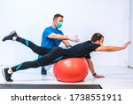 Small photo of Physiotherapist with mask and a patient stretching on a ball. Physiotherapy with protective measures for the Coronavirus pandemic, COVID-19. Osteopathy, sports chiromassage