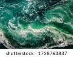 Small photo of Abstract background. Waves of water of the river and the sea meet each other during high tide and low tide. Whirlpools of the maelstrom of Saltstraumen, Nordland, Norway