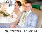 Portrait smiling groom and bride in wedding car - stock photo