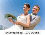 Portrait smiling groom and bride against blue sky - stock photo