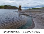 Abandoned buildings. An abandoned lighthouse near the shore. Forest lake with an abandoned building. Lake with rocky shores. A lake with rocky shores overgrown with pine trees. - stock photo
