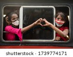 Small photo of MUMBAI/INDIA - MAY 24, 2020: Family member of migrant workers sit in a bus gives a heart sign outside railway terminus while waiting for their train during a nationwide lockdown.
