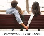 Small photo of Love Triangle. Cheating Boyfriend Hugging Girlfriend Holding Hands With Her Girl Friend Sitting On Bench Together In Park Outdoor. Back-View