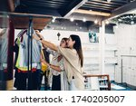 Small photo of Attractive Caucasian friends enjoying leisure time for merchandise shopping during big Brack Friday discounts, beautiful hipster girls with hangers discussing quality and design of purchase clothing