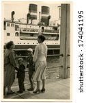 Small photo of GERMANY, BUNG FEHMAN - 1970s: An antique photo shows Two women with two boys standing on the pier and look at the passenger ship