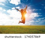 happy young woman jumping over... | Shutterstock . vector #174057869