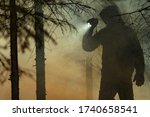 Rescue Search. Men Wearing Camouflage Clothing with Powerful Flashlight Between Trees and Fire Smoke. Forest Wildfire Rescue Mission.  - stock photo