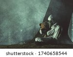Men in White Hazmat Suite and Gas Mask Laying Under the Tree with His Daughter Teddy Bear Toy Next to Him. Dark Night in Forest Covered by Smoke. - stock photo