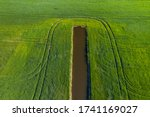 Small photo of Land improvement or land amelioration concept, drone flying over narrow irrigation or drainage channels on rye or wheat field. Illustration of agriculture in the zone of risky agriculture.