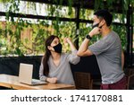 Small photo of Asian woman and man friends wearing face mask outdoors. Friends greeting and shaking with elbows as new normal. Corona Virus - Covid 19 elbow bumps greeting style to prevent contact and virus spread.