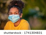 Small photo of Mixed race African American teenager teen girl young woman wearing a face mask outside during the Coronavirus COVID-19 virus pandemic