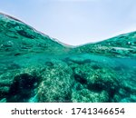 Split underwater view of a rocky sea bed under a blue sky - stock photo