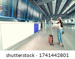 Small photo of Asian female wearing face mask with suitcase checking flight cancellation status on airport information board in empty airport. airline bankrupt, airline crisis, coronavirus or new normal concept