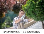 Gardening time. Happy dark-haired male in protective gloves trimming tree branches in the yard, smiling - stock photo