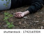 Murder in the woods. The hand of a dead woman in a tracksuit lies in the forest on the ground. The concept of violence against women. Horizontal photo. Close up.