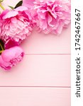 Small photo of Purpure peony flowers on pink wooden background. Top view