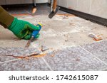 Small photo of dismantling of tile. Hands in green working gloves undermine the tile with a chisel and a hammer