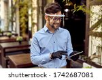 Small photo of Happy waiter using digital tablet while wearing visor and protective gloves at outdoor cafe.
