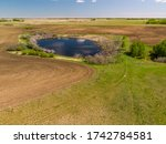 An aerial view of a calm secluded peaceful pond surrounded by trees and other natural growth in the wide open prairies of Saskatchewan, Canada.