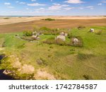 Aerial view of farm houses and various other structures that were built by the first farming settlers in the Prairie Province of Saskatchewan, Canada. Many buildings date back to the early 1900