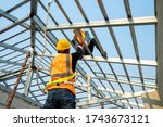 Builder Working On Roof Of New...