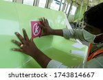 Small photo of MUMBAI/INDIA -MAY 28, 2020: Worker fixes a sticker showing the measures for the social distancing as a preventive measure against the COVID-19 corona virus. MMRDA is preparing to resume its services