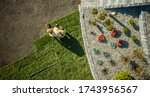 Landscaping and Gardening. Aerial View of Gardener Installing Brand New Grass in Newly Developed Residential Garden. Industrial Theme. - stock photo