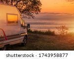 Waterfront RV Camping Site. Camper Van Road Travel. Scenic Sunset in Calm Sea Front Place. Recreational Vehicles Theme. Travel Industry. - stock photo