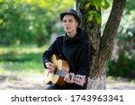 A Teenage Boy Plays Guitar On...