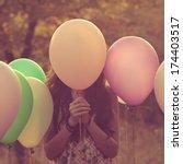 Stock photo girl hiding behind the balloon 174403517