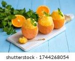 Small photo of Citrus Mint Sorbet. Iced mint, orange and lemon granita in frozen lemon cups on light blue wooden background. Selective focus.